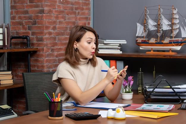 Vista frontale di una bella donna che prende appunti lavorando in ufficio