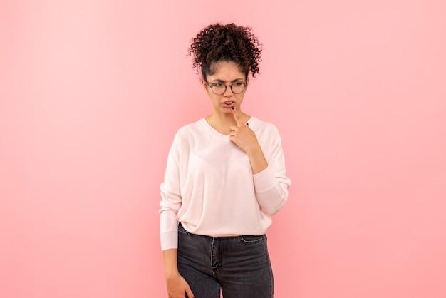 Vista frontale della donna graziosa che pensa sulla parete rosa