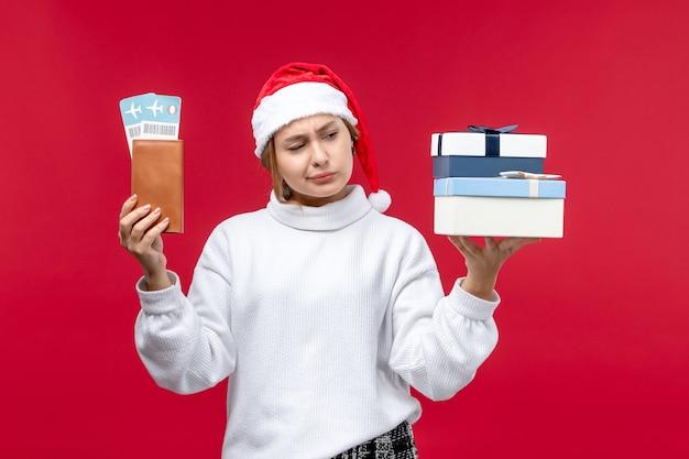 Вид спереди красивая женщина с подарками и билетами на красном фоне