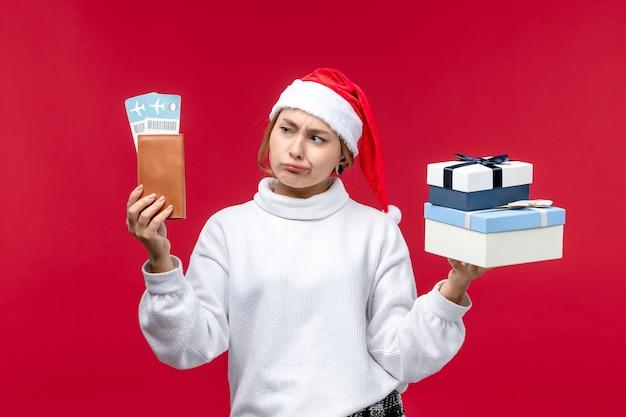 Donna graziosa di vista frontale con regali e biglietti su priorità bassa rossa