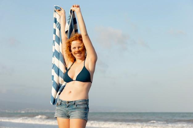 Ragazza graziosa di vista frontale che sorride alla spiaggia