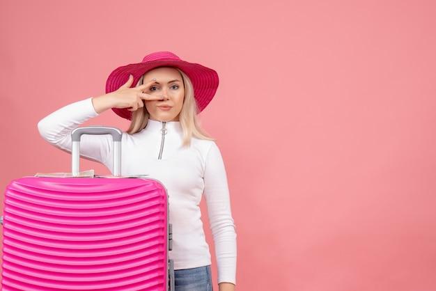 핑크 가방 뒤에 서있는 전면보기 꽤 젊은 아가씨