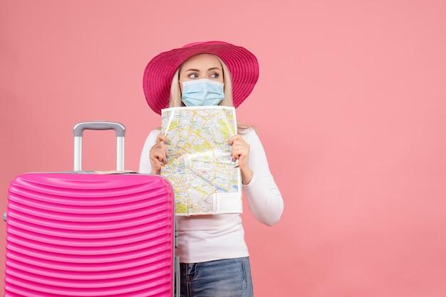 Вид спереди симпатичная молодая леди, стоящая возле чемодана с картой