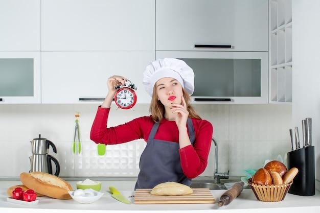 正面図キッチンで赤い目覚まし時計を保持しているかなり若い女性