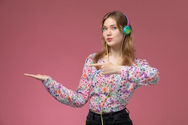 Vista frontale piuttosto giovane donna mostra la sua mano vuota e sorprese sul muro rosa scuro