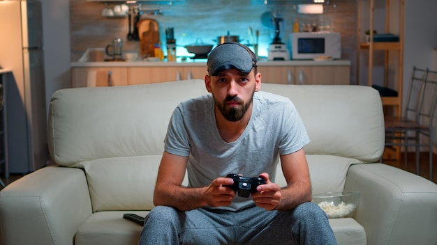 Front view of pro gamer sitting on sofa in front of television while playing videogames competition