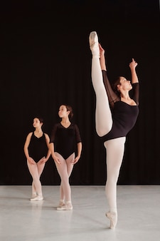 Front view of professional ballet dancers practicing together while wearing pointe shoes