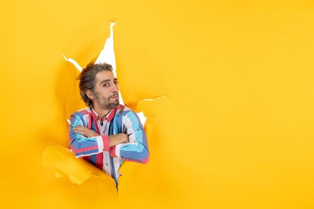 Vista frontale di un giovane orgoglioso e ambizioso che posa per la telecamera attraverso un buco strappato in carta gialla