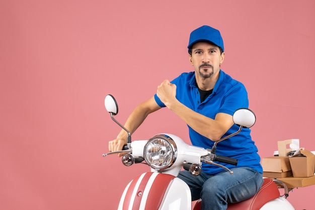 Front view of proud courier guy wearing hat sitting on scooter on pastel peach background