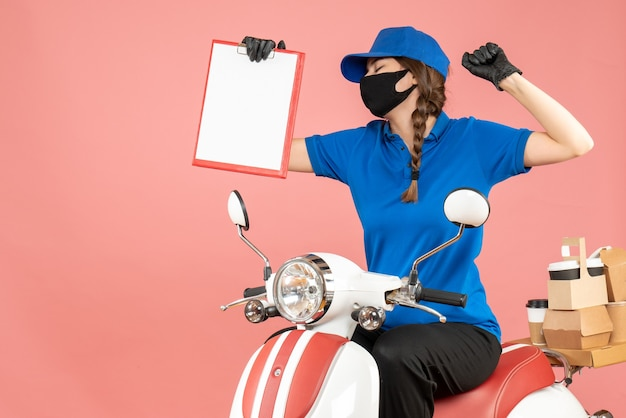 Front view of proud courier woman wearing medical mask and gloves sitting on scooter holding empty paper sheets delivering orders on pastel peach background