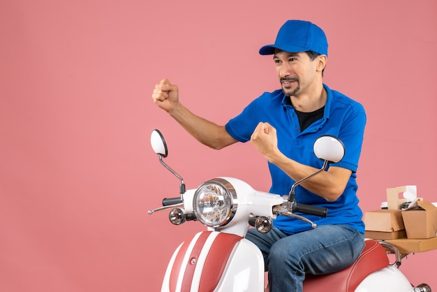 Front view of proud delivery guy wearing hat sitting on scooter on pastel peach background
