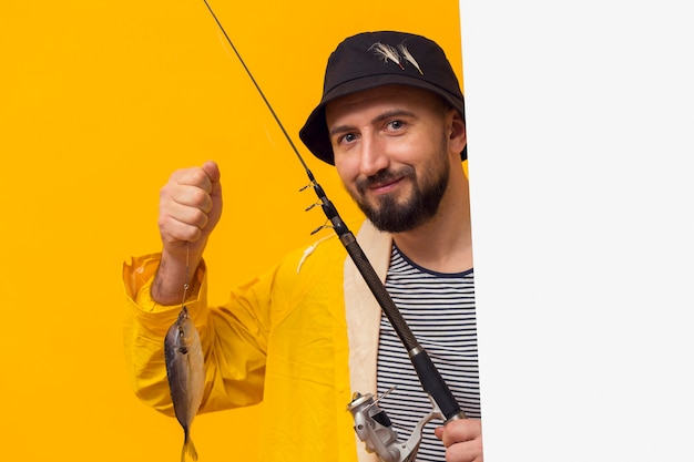 Front view of proud fisherman holding fishing rod with catch
