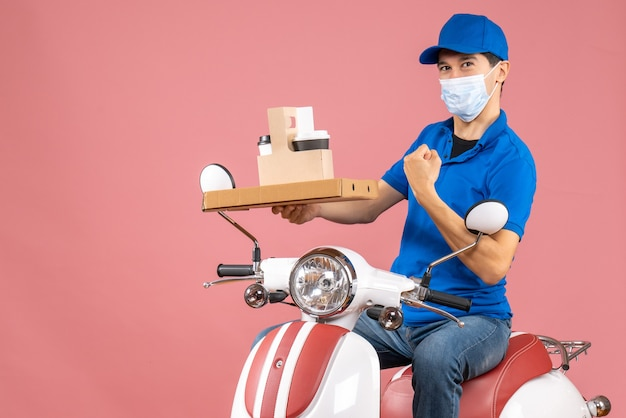 Front view of proud male delivery person in mask wearing hat sitting on scooter delivering orders on pastel peach background