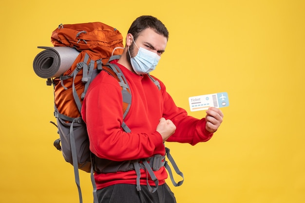 Front view of proud traveller guy wearing medical mask with backpack and showing ticket on yellow background