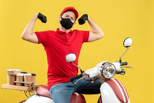 Vista frontale di orgoglioso giovane adulto che indossa camicia rossa e guanti cappello in maschera medica offrendo ordine seduto su uno scooter che mostra la sua muscolatura su sfondo giallo