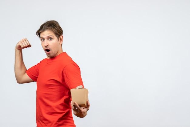 Vista frontale del giovane ragazzo orgoglioso in camicetta rossa che tiene piccola scatola su priorità bassa bianca