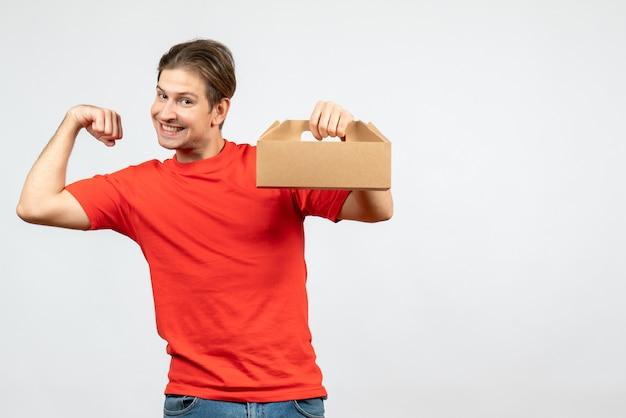 Vista frontale del giovane orgoglioso che mostra la sua scatola di contenimento muscolare in camicetta rossa su sfondo bianco