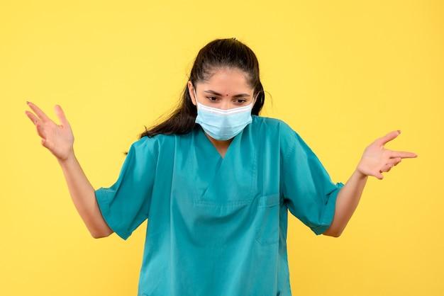 黄色の背景に彼女の手を開いているマスクを持つ女性医師を詮索好きな正面図