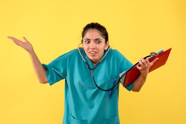 黄色の背景に紙を保持している制服を開いた手で女性医師を詮索