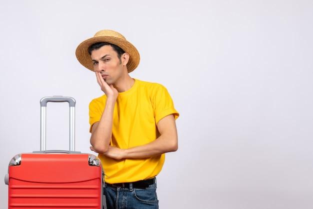黄色のtシャツと麦わら帽子で若い男を詮索好きな正面図