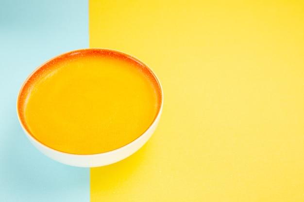 Zuppa di zucca vista frontale all'interno del piatto sul colore del piatto di minestra da tavola giallo-blu