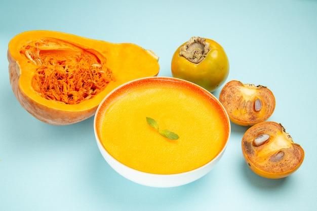 青いテーブル皿の色のスープに新鮮なカボチャと正面図のカボチャスープ