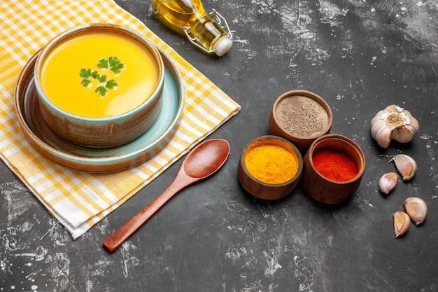 Тыквенный суп с чесноком и маслом на темном столе, вид спереди