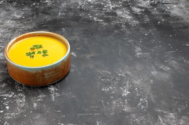 어두운 테이블에 접시 안에 채소와 전면보기 호박 수프