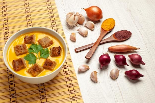 白いスペースに小さなパンのラスクとニンニクが入った正面かぼちゃのスープ