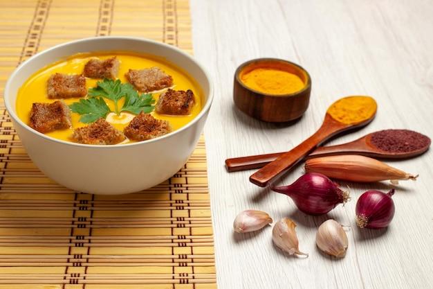 Тыквенный суп, вид спереди, с сухарями и чесноком на белом пространстве