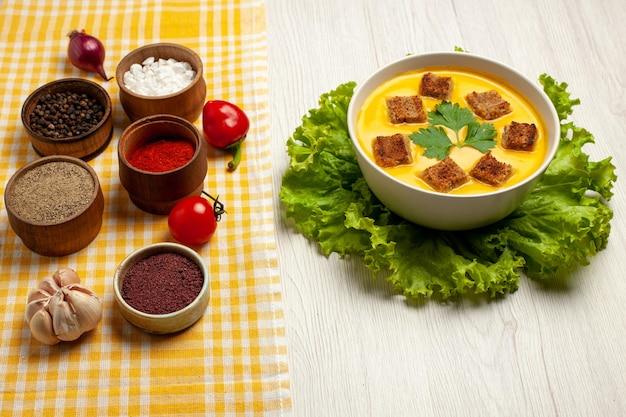 白いスペースに小さなラスクと調味料を入れた正面カボチャ スープ