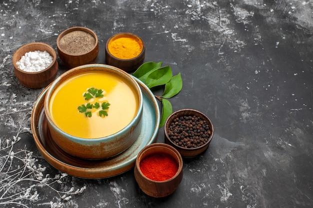 暗いテーブルに調味料を入れた正面図のカボチャスープ