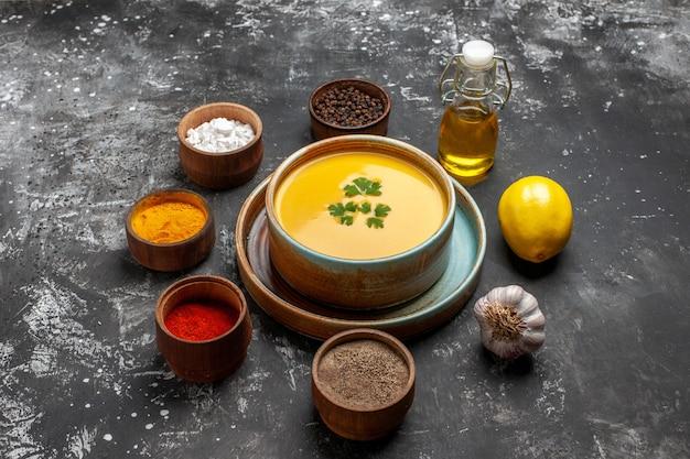 Тыквенный суп с приправами на темном столе, вид спереди