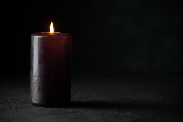 Vista frontale della candela viola su oscurità