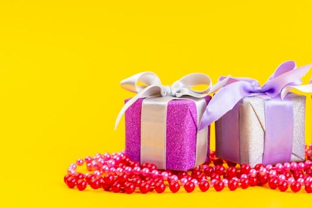Una vista frontale viola confezioni regalo con fiocchi su giallo