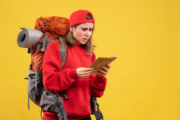 Озадаченная туристка-женщина, глядя на карту путешествия, вид спереди