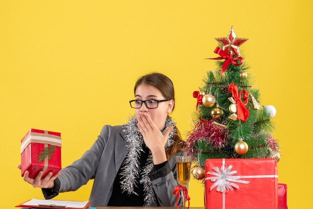 Vista frontale ragazza perplessa con gli occhiali seduti al tavolo guardando il suo regalo albero di natale e regali cocktail