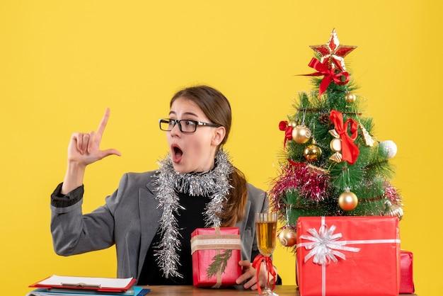 Vista frontale ragazza perplessa con gli occhiali seduto al tavolo che punta con il dito su albero di natale e regali cocktail