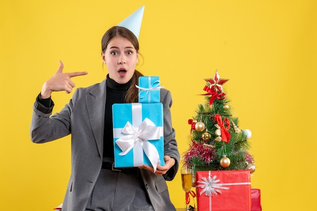 Ragazza perplessa vista frontale con tappo del partito che tiene i regali di natale vicino all'albero di natale e cocktail di regali