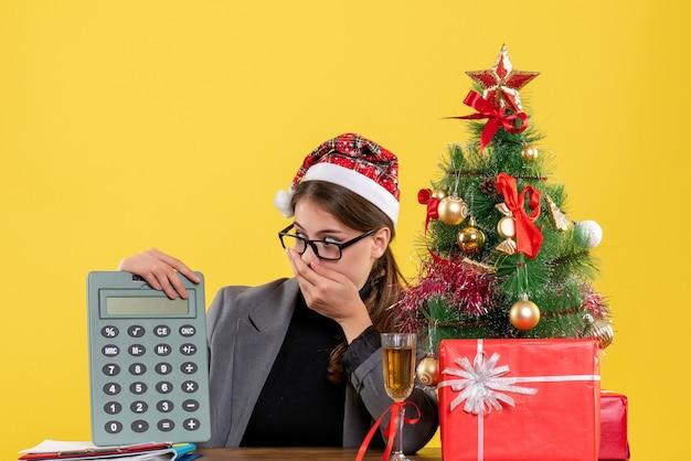 Ragazza perplessa di vista frontale con il cappello di natale che si siede al tavolo loooking all'albero di natale del calcolatore e al cocktail dei regali