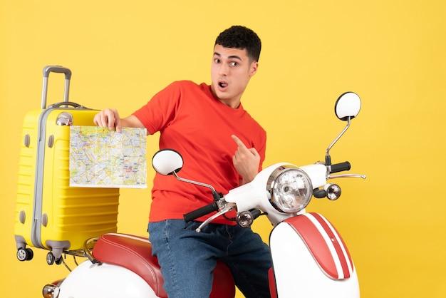 Vista frontale perplesso bell'uomo sulla mappa della holding del ciclomotore