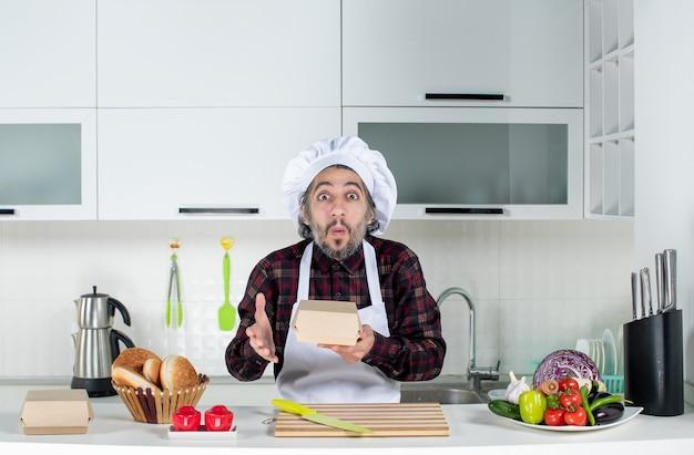 Vista frontale dello chef maschio perplesso in scatola di contenimento uniforme in cucina