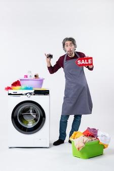 Вид спереди озадаченный мужчина держит карточку и знак продажи, стоящий возле корзины для белья стиральной машины на белой стене