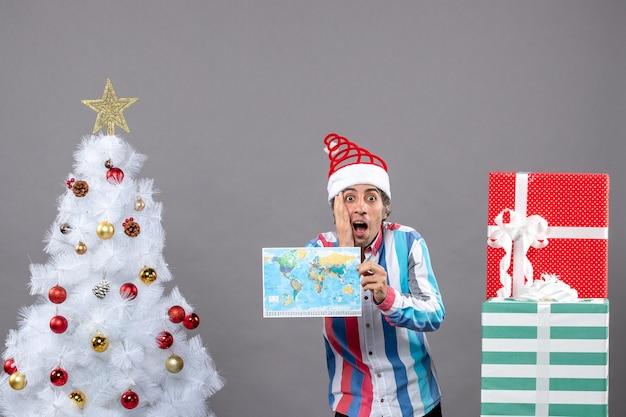 나선형 봄 산타 모자와 그의 얼굴에 손을 넣어지도를 들고 스트라이프 셔츠와 전면보기 의아해 남자