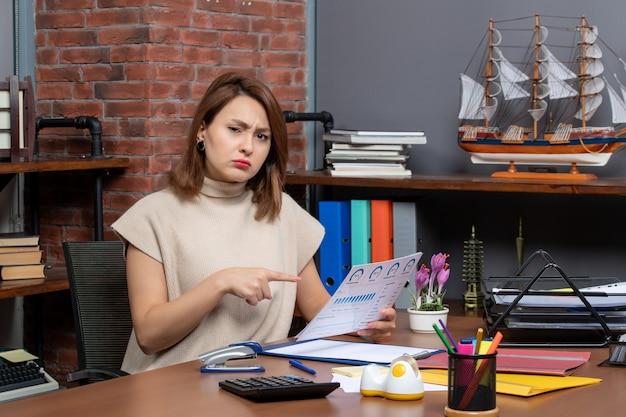 Vista frontale della donna graziosa perplessa che tiene i documenti che lavorano in ufficio