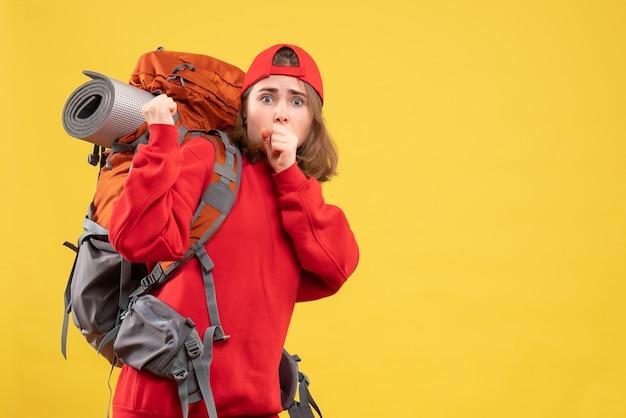 Donna di viaggiatore perplesso vista frontale in zaino rosso in piedi sulla parete gialla