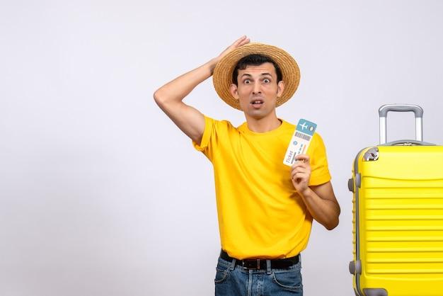 Вид спереди озадаченный молодой человек в желтой футболке, стоящий возле чемодана с билетом