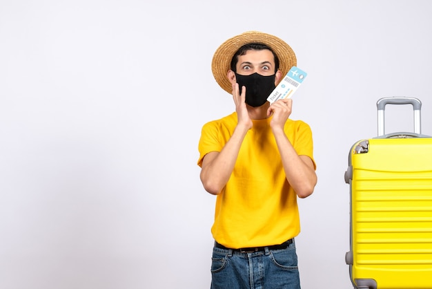 Front view puzzled young man in yellow t-shirt standing near yellow suitcase holding up travel ticket