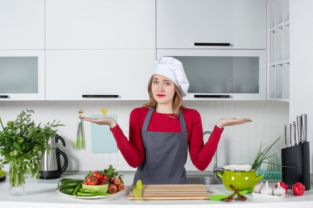 Front view puzzled young woman in apron standing behind table
