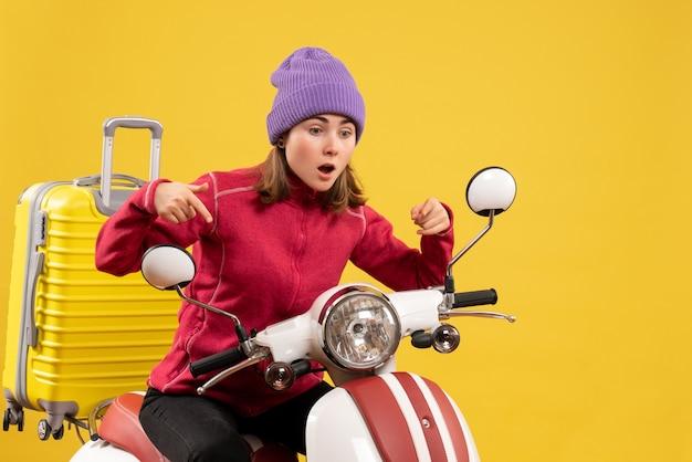 Vista frontale perplessa giovane donna sul ciclomotore che punta a qualcosa